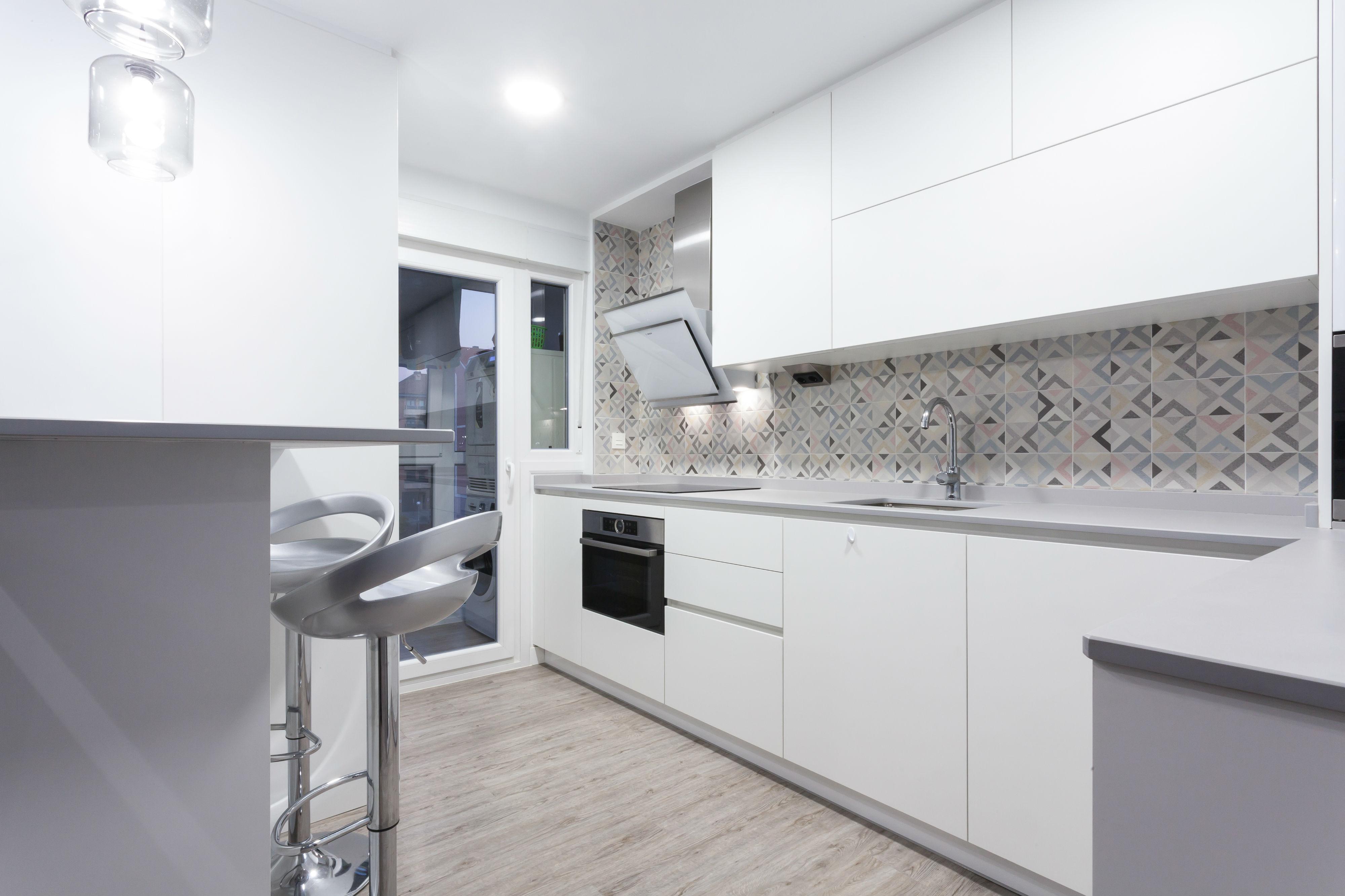 Cocina americana reformada en una vivienda de Galdakao con los muebles lacados en blanco